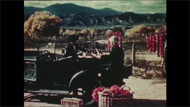 1940s: UNITED STATES: red chillies drying in sun on Mexican ranch. Man and truck. Chill in basket.