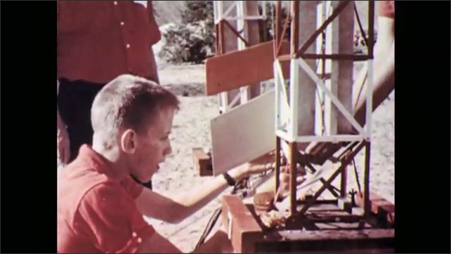 1960s: Boy puts part into rocket. Boys put rocket on launcher. Close up, hand lowers rocket. View of loudspeaker. Canted angle, rocket launchers. Man talks into microphone.