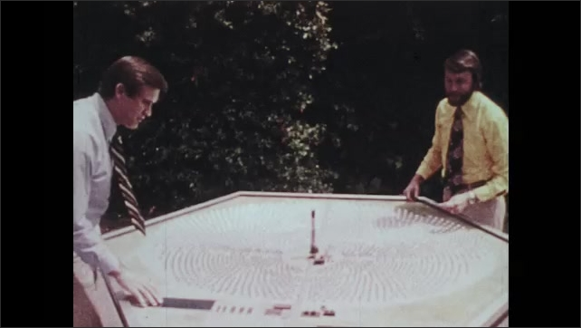 1970s: Motorized mirrors spin and move on solar energy farm. Men talk and observe model of solar energy power plant.