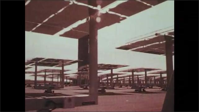 1970s: Heliostat mirror turns toward sun. Metal rods spin. Mirror turns toward ground. Men and trucks work among large group of heliostat mirrors.