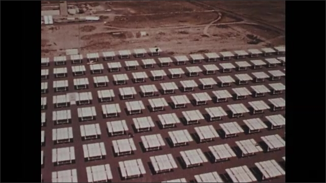 1970s: Large field of heliostat mirrors in desert. Mirror reflects solar energy power plant in desert.