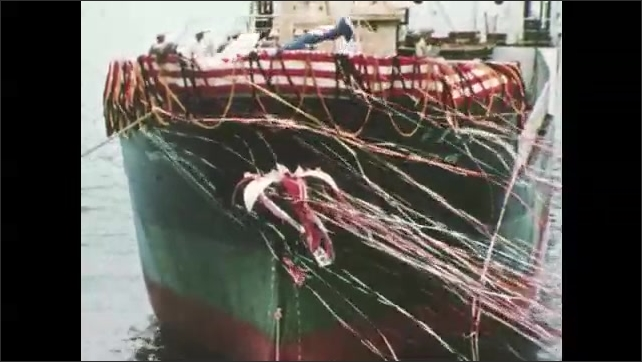 1980s: Man on podium smashes object.  Ball on ship opens to release streamers.  Spectators.  Ship moves through water.