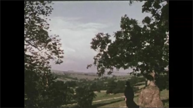 1950s: Man on hill overlooking valley. View of valley. View of hills.