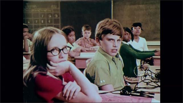 1970s: Kids sitting at desks, woman in foreground. Woman talking. View through brokem window, bus driving. Kids at desks, look forward. Woman talking in front of kids.
