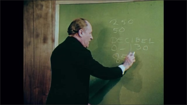 1970s: Cars driving on street. Trucks driving on city street. Man writes on chalkboard, talks into camera.