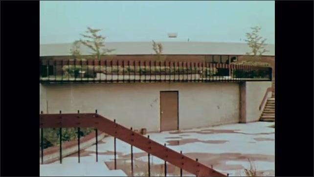 1970s: Pan across exterior of building. Pan across courtyard.