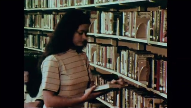 1970s: Tracking shot, follwing students through hallway. Girl takes book from shelf, zoom out to kids at tables, girl sits. Man at desk talks into camera.