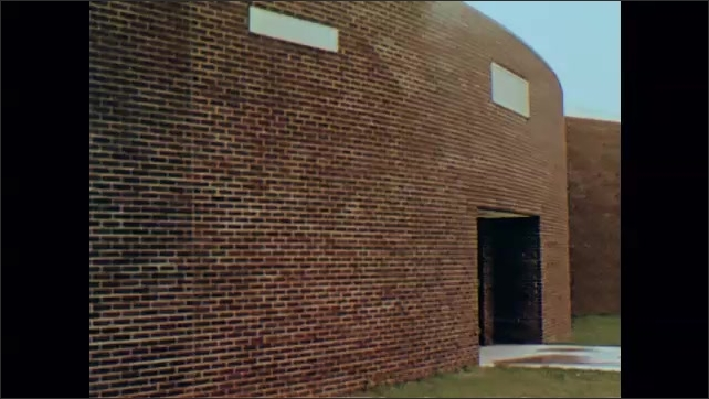 1970s: Man sitting with teen boys in courtyard, man and boys stand and walk toward building. Exterior shots of buildings.