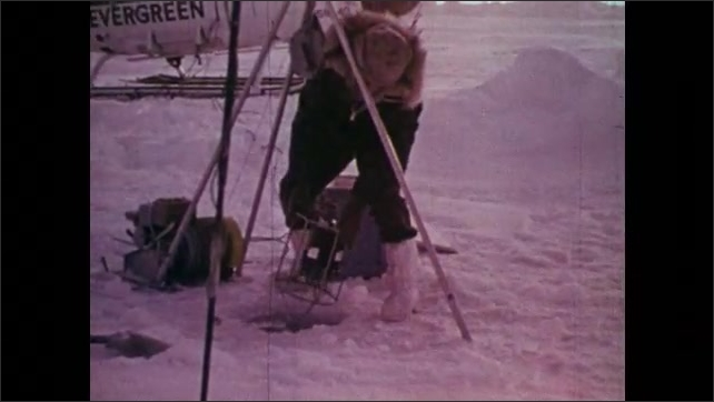 1970s: UNITED STATES: buoy in water. View across sea. Man collects water composition sample through ice.