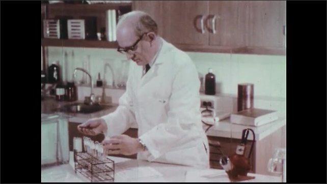 1970s: Doctor and nurse talk in hospital room. Doctor holds jug of disinfectant. Scientist tests fluid from test tubes. Scientist waves heat gun near fluid samples.