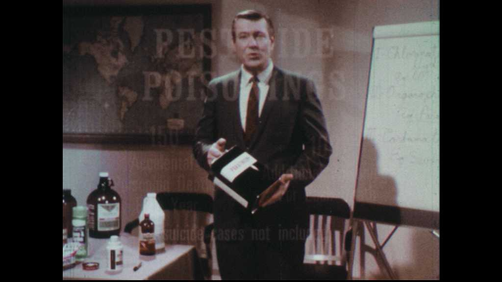 1970s: Man holds cannister of parathion and speaks. Man places cannister on table. Man stands in classroom and speaks. Man stands near easel and table of bottles and speaks.