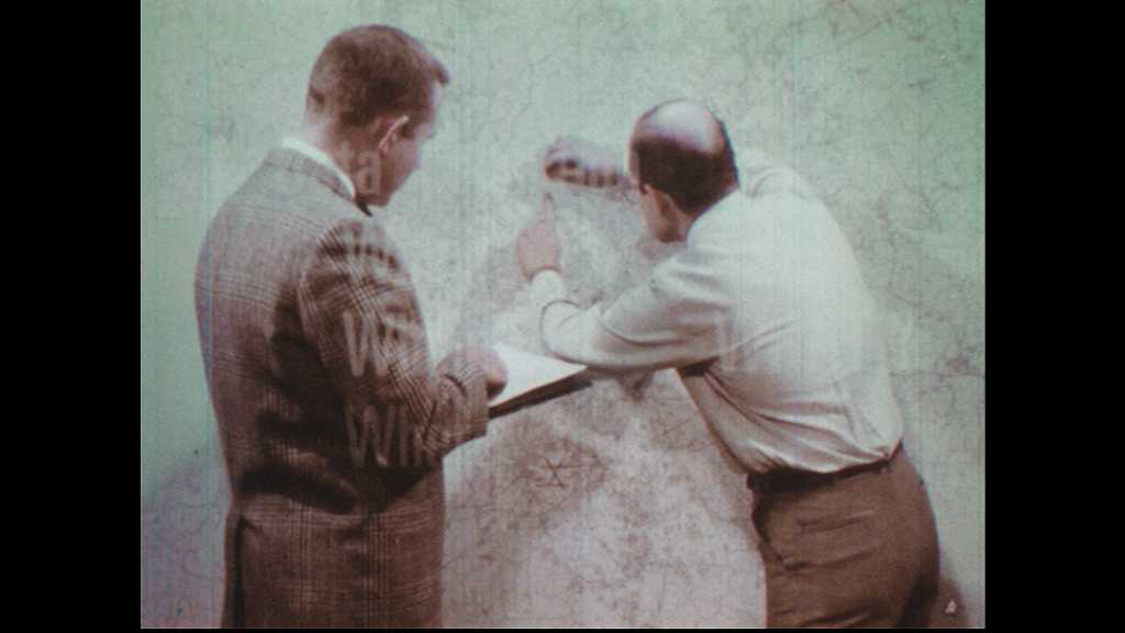 1970s: Men place pins on large wall map. Men point to map and speak. Pins in large city map.