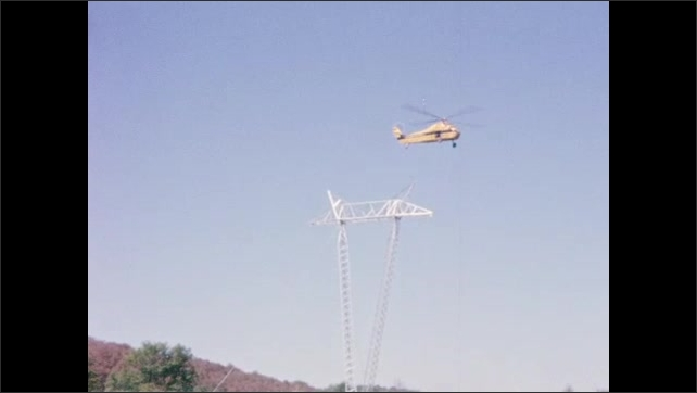 1960s: UNITED STATES: helicopter holds frame in place as men tighten cables to ground