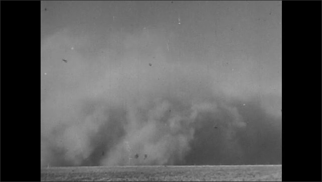 1940s: UNITED STATES: View across landscape. Dust cloud blows across land. Man runs from house.