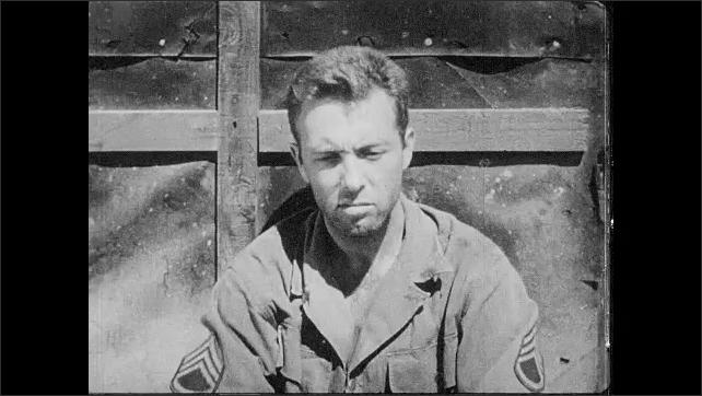 1950s: UNITED STATES: soldier sits on ground in prison camp. Sergeant in prisoner of war camp.