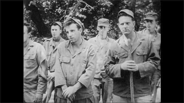 1950s: UNITED STATES: soldiers call out names. Role call and head count at end of day. Detail marches back to POW compound