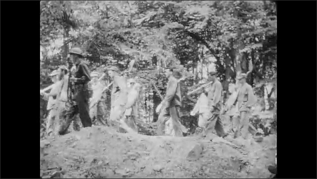 1950s: UNITED STATES: head count and role call of prisoners of war during work detail. Prisoners of war march back to compound. Prisoner hides in tunnel.