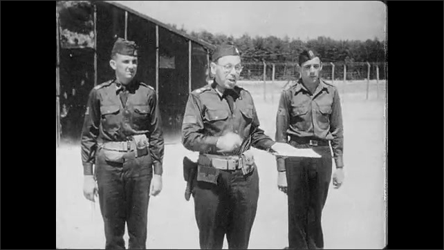 1950s: UNITED STATES: prisoners of war talk to guards in camp. Guard with papers for soldiers to sign