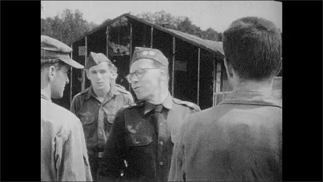1950s: UNITED STATES: guard speaks to prisoners in line. Guard threatens prisoners.