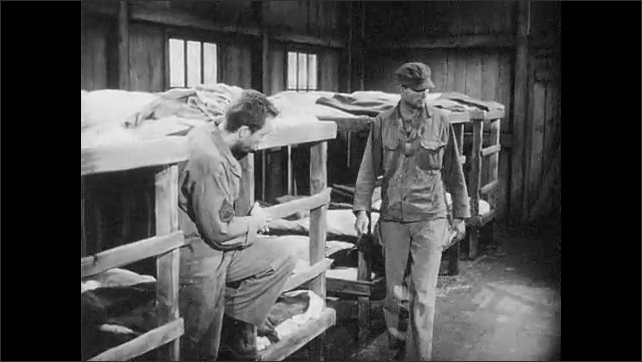 1950s: UNITED STATES: prisoner of war removes wood from bunk bed. Prisoners in dorm room. Key in hand. Key to tool house