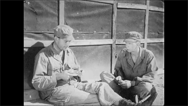 1950s: UNITED STATES: soldier eats by hut. Soldier eats soup. Soldier puts bread in pocket.
