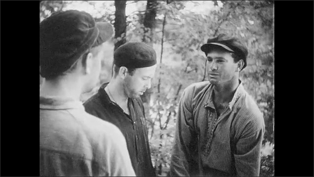 1950s: UNITED STATES: man carries tools. Men hide in woods