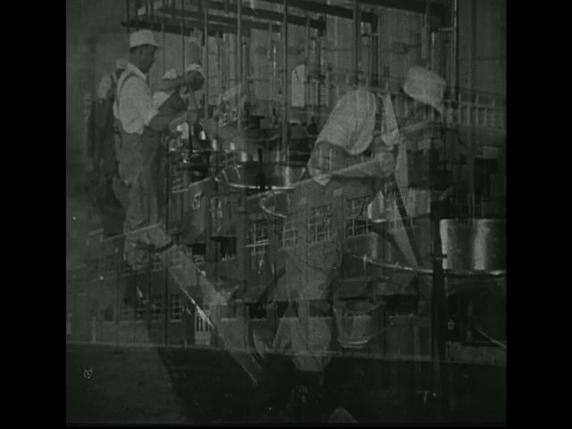 Factory workers clean vessels and other materials used for processing.