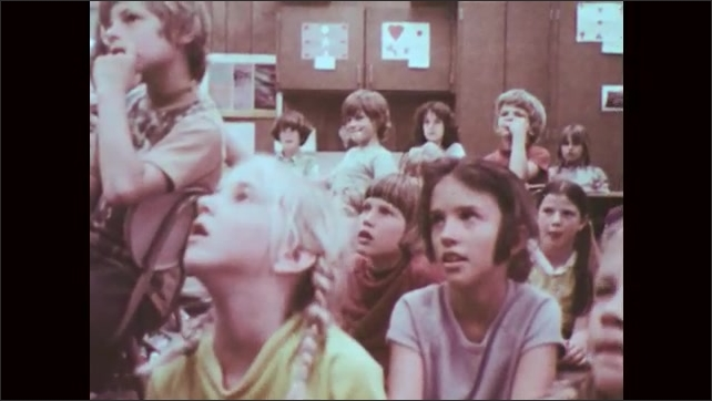 1970s: UNITED STATES: close up of girl in class smiling. Traffic safety ranger visits school. Students listen to man speaking. Man shows paper to fourth graders.
