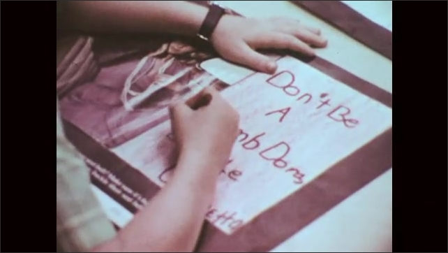 1970s: UNITED STATES: students create art work about traffic safety. Girl smiles at desk. View of highway. Wrong Way sign
