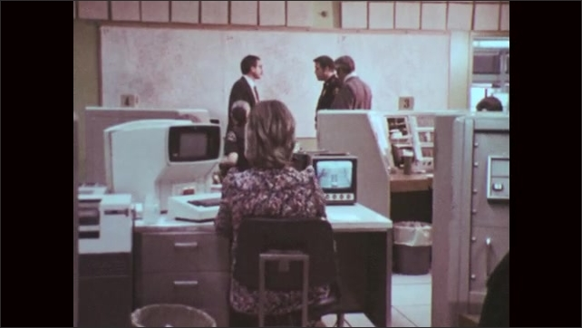 1970s: UNITED STATES: man speaks to people in computer room in Dallas, Texas. Map on wall. Lady works at computer. Monitor on table.