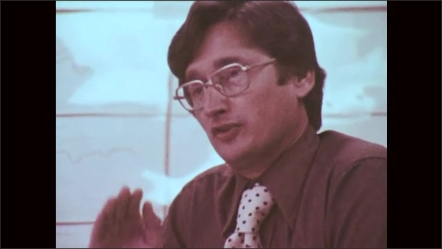 1970s: UNITED STATES: man wearing glasses speaks at meeting. Man with spotted tie. Close up of man's face.
