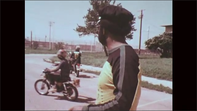 1970s: Man talking, boys riding motorcycles in background.