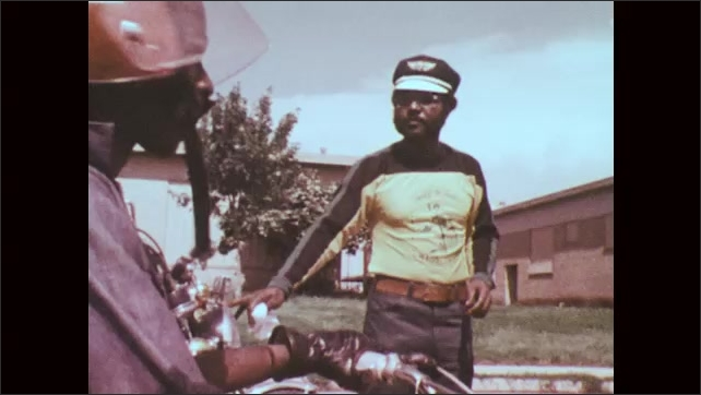 1970s: Man in street, zoom out to boy on motorcycle in foreground, man walks to boys on motorcycles.