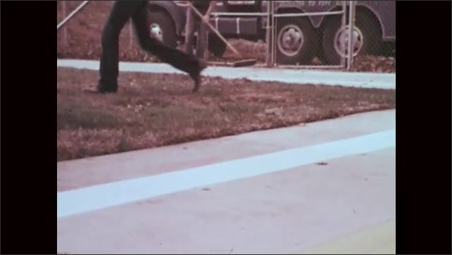 1970s: Close up, wheel drives toward camera. Machine painting stripes on pavement, zoom out to maintenance workers in yard,