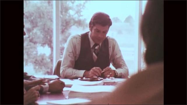 1970s: Man sitting at table. Close up of man talking. Man talking at table.