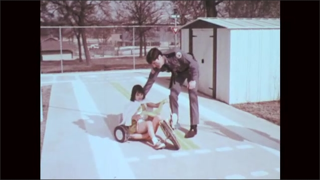 1970s: Shots of boys riding tricycles. Mna blows whistle, zoom out, man stops girl on tricycle. Kids walking by stop sign.