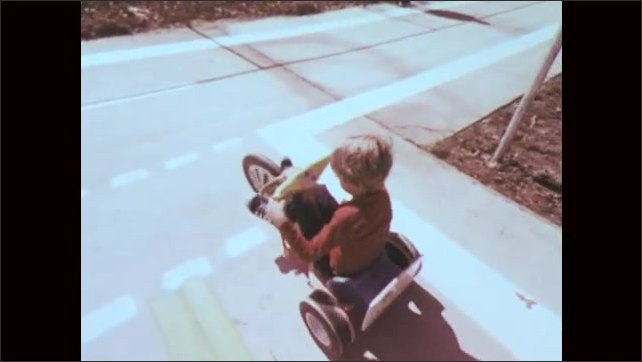 1970s: Kids riding tricycles. Man blows whistle, yells. Girl rides tricycle past boys. Kids on tricycles crash. Boy stops tricycle at sign. Man walking, zoom out to kids riding tricycles on course.