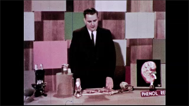 1960s: Petri dish of reddish clear liquid is aerated by tube pushing air bubbles. Man stands at laboratory table with various equipment, including air pump with running motor. Man talks.