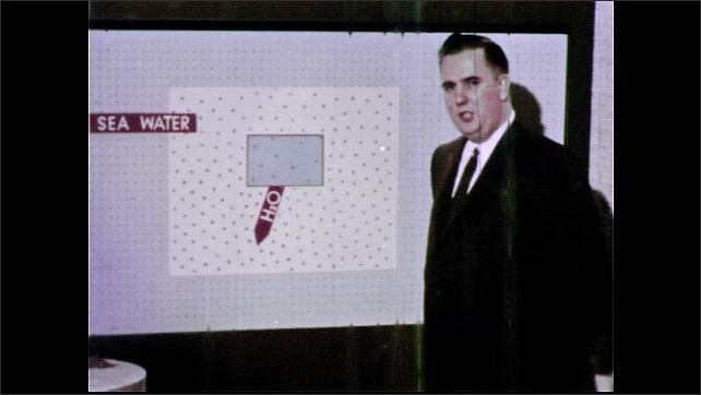 1960s: UNITED STATES: man looks at camera during presentation. Water loss from cell drawing. Man places arrows on diagram