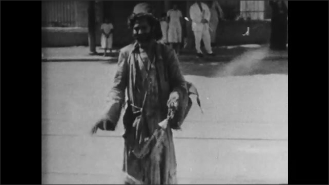 1930s: Intertitle ????uli Guli men, street fakirs of the mystic East???? Man stands on a busy street, holds an incense burner, shakes it and smoke comes out. Hand puts something on the incense burner.
