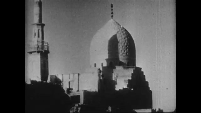 1930s: Intertitle. Two people walk next to a giant Arab building. Arab tower. Camels stand in front of a building, a man sweeps the floor.