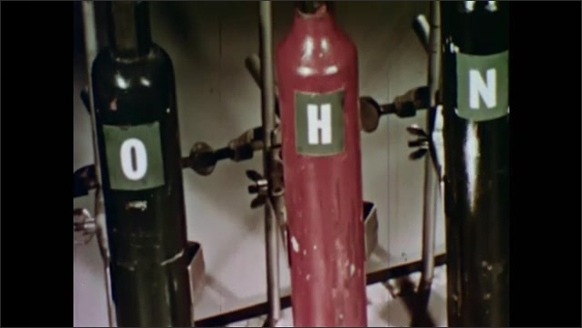 1950s: pouring liquid into empty beaker in front of canisters of hydrogen, nitrogen, oxygen