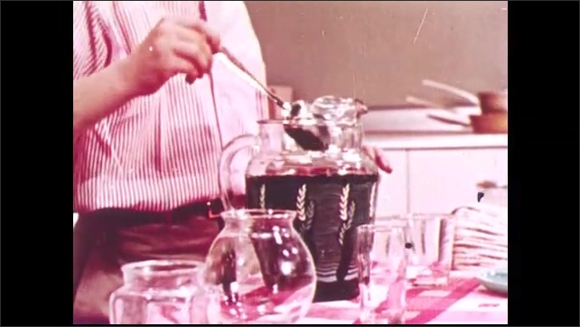 1950s: UNITED STATES: boy adds colouring to water in jug. Boy stirs liquid in jug with spoon. Boy pours water into container