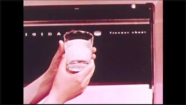 1950s: UNITED STATES: hands opens ice compartment in freezer. Hand brings out glass from freezer. Ice in glass
