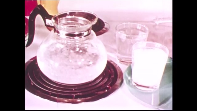 1950s: UNITED STATES: water boils in container. Three states of water. Water as solid, liquid, and gas. Boy puts lid on jar. Boy puts jar in water
