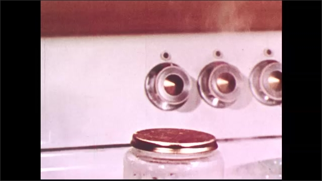 1950s: UNITED STATES: jar and lid inside hot pan. Steam around jar. Cap blows off jar