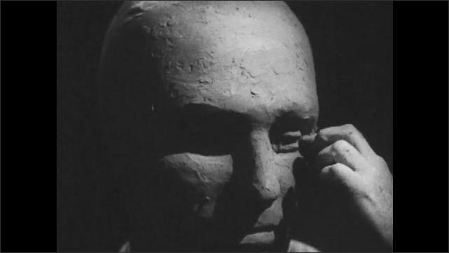 1950s: Close up, hands sculpting clay head.