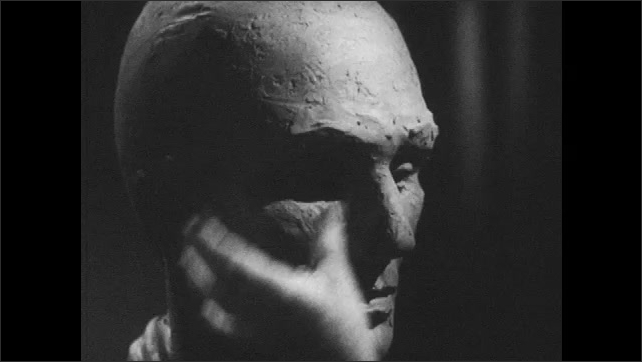 1950s: Close up, hands sculpting clay head. Rear view of clay bust, hands sculpting.