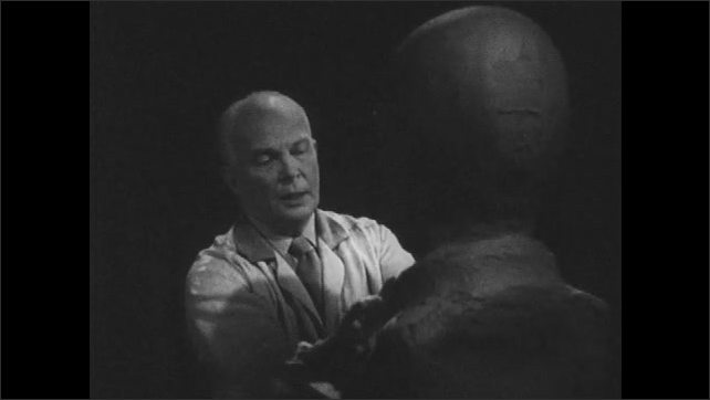 1950s: Close up of man. Man sculpting clay bust, camera tracks to other side of bust.