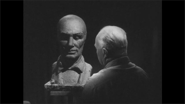 1950s: Man sculpting clay bust. Rear view, man sculpting, man turns to camera, adds ears to sculpture.